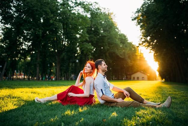 Amour couple est assis sur une herbe dans le parc d'été. date romantique de jolie femme et jeune homme