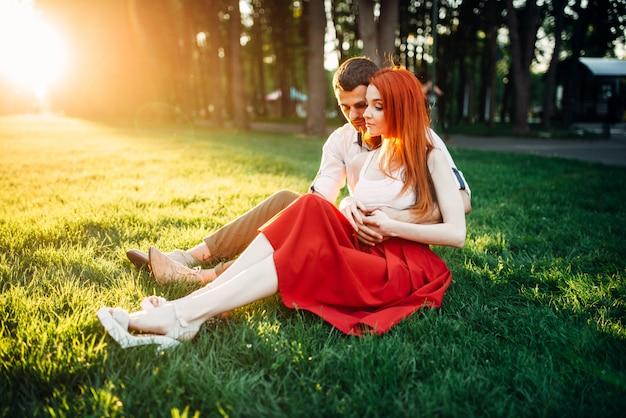 Amour couple est assis sur l'herbe dans le parc, rendez-vous romantique