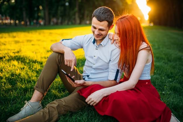 Amour couple heureux ensemble, rendez-vous romantique dans le parc d'été au coucher du soleil. jolie femme et jeune homme de loisirs sur l'herbe