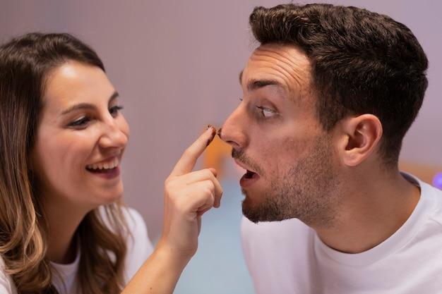 Amour couple jouant avec du chocolat