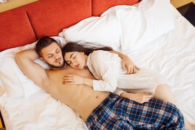 Amour couple en pyjama dormant dans son lit à la maison, bonjour. relation harmonieuse dans la jeune famille