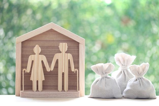 Amour couple senior avec maison modèle et pièces d'argent dans le sac sur fond vert naturel