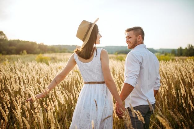 Amour couple tenir la main, marcher dans un champ de seigle