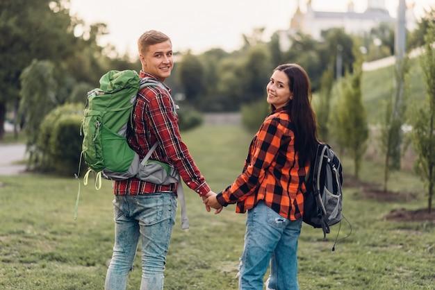Amour couple de touristes avec des sacs à dos main dans la main, bonnes vacances. aventure estivale de jeune homme et femme, marchant dans le parc de la ville
