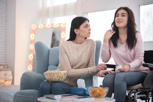 Amour dramatique. sœur sombre et femme immobile regardant un film et ayant des larmes