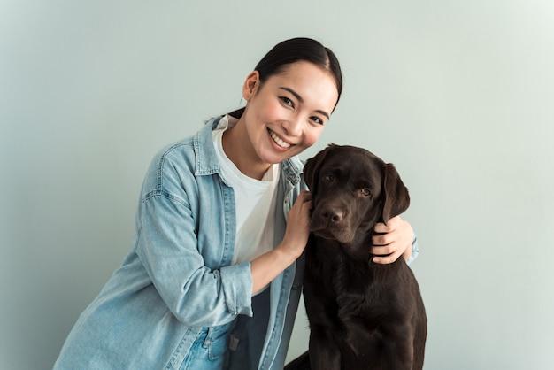 Amour entre propriétaire et chien. femme aimante caressant son animal de compagnie sur un fond de mur gris. concept - fidèle ami de l'homme chien