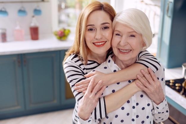 Amour de fille. enthousiaste jeune femme étreignant sa mère âgée et souriant à la caméra joyeusement avec elle en se tenant debout dans la cuisine
