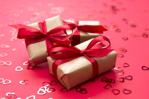 Amour, fond de la saint-valentin. coffret cadeau enveloppé de papier kraft et arc rouge isolé sur fond rouge.