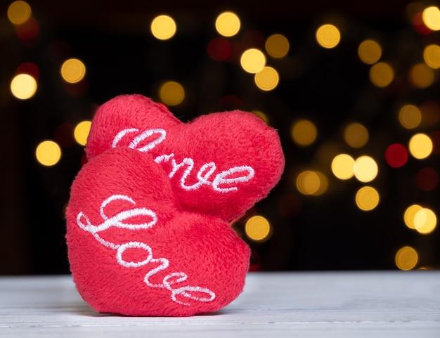 Amour en forme de coeur rouge sur bois blanc avec bokeh coloré