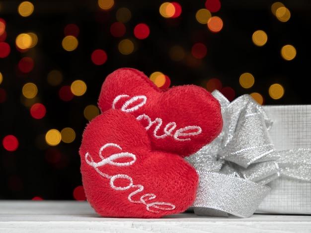 Amour en forme de coeur rouge et boîte-cadeau en argent sur bois blanc avec bokeh coloré