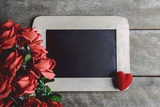 Amour forme de coeurs, roses rouges et tableau vide de craie sur fond de bois