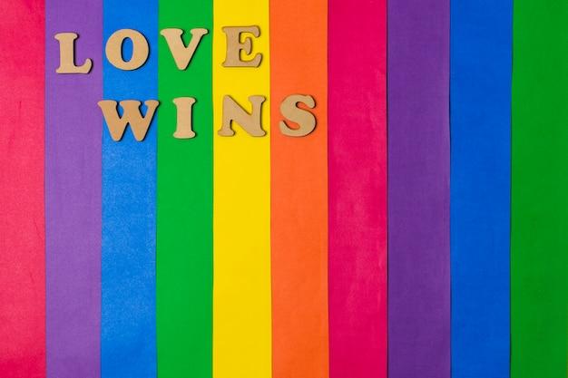 L'amour gagne les mots et le drapeau gay brillant