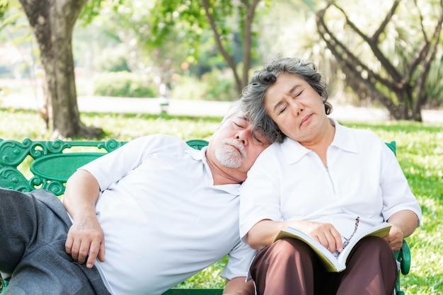 Amour heureux couple de personnes âgées dormant ensemble , couple de personnes âgées se relaxant , son mari s'est endormi sur son épaule dans un parc naturel