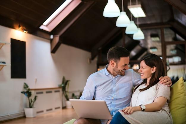 En amour, jeune couple à l'aide d'un ordinateur portable assis sur un canapé