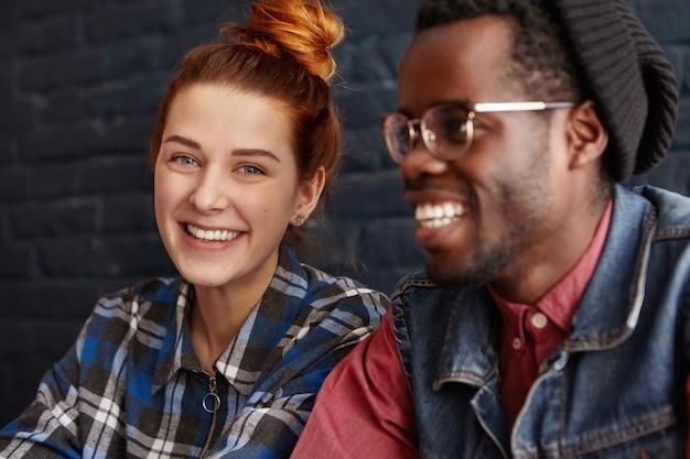 Amour, jeunesse et amitié. jolie femme aux cheveux roux vêtue d'une chemise à carreaux bleue à la recherche avec un sourire mignon