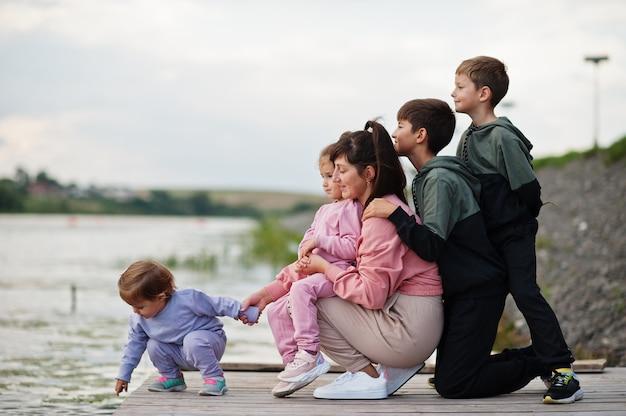 L'amour maternel. maman avec quatre enfants en plein air sur la jetée. les sportifs en famille nombreuse passent leur temps libre à l'extérieur.