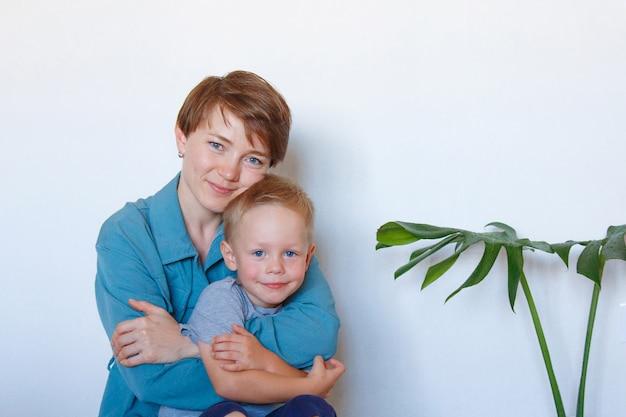 L'amour d'une mère. une maman heureuse avec son fils en vêtements bleus embrasse. copie espace.