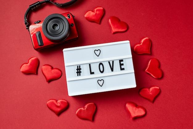 Amour message lightbox avec coeurs rouges, caméra rouge. flatlay vue de dessus.