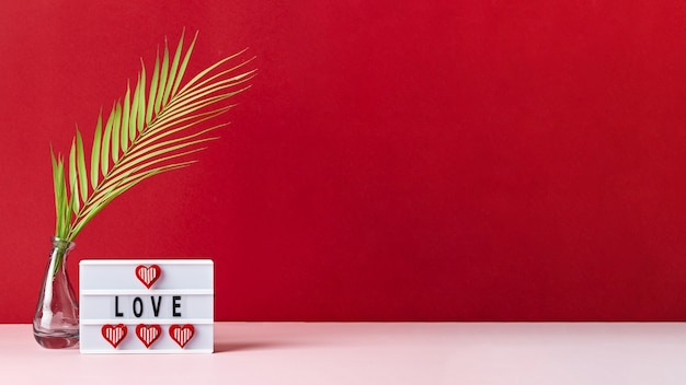 Amour message lightbox avec coeurs rouges et feuille de palmier