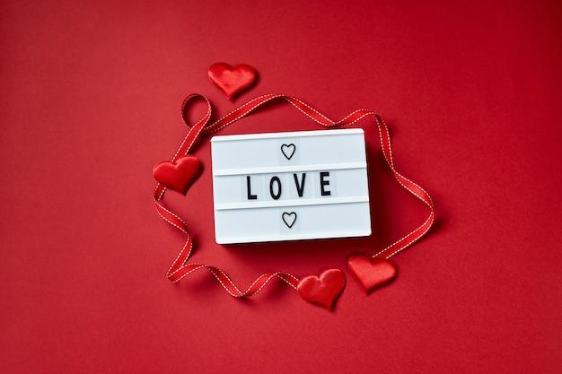 Amour message lightbox avec des coeurs rouges. flatlay vue de dessus.
