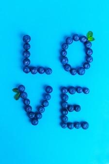 Amour de mot à base de bleuets à la menthe sur une surface bleue
