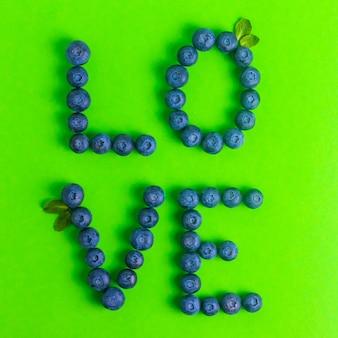Amour de mot à base de bleuets à la menthe sur une surface verte