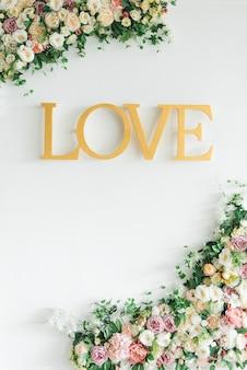 Amour de mot avec bordure de roses sur pastel, vue de dessus avec fond. saint valentin ou amour abstrait