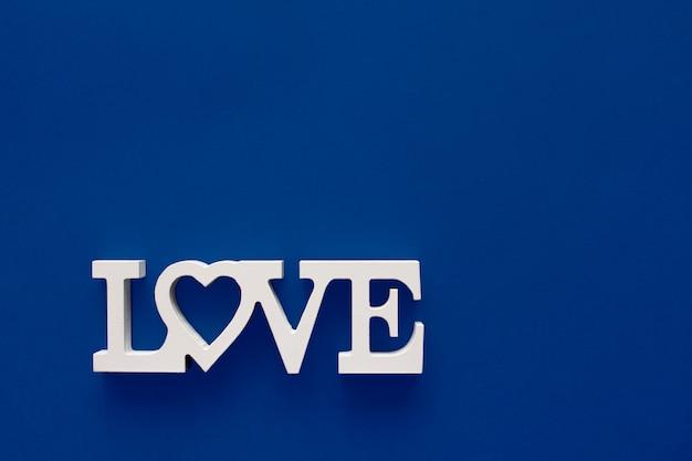 Amour de mot fait de lettres blanches en bois situées sur un fond bleu clair