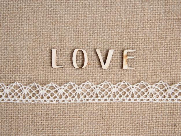 Amour de mot sur la toile de jute avec bordure en dentelle