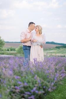 Amour, noces d'argent. heureux couple caucasien mature romantique, posant ensemble en se regardant, tout en marchant à l'extérieur dans un magnifique champ de lavande