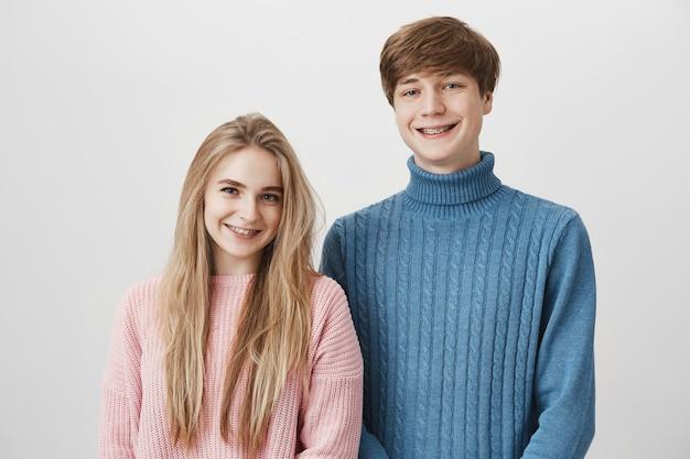 Amour, relations, romance et bonheur. beau jeune couple posant contre l'espace gris