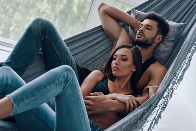 Amour sans fin. vue de dessus du beau jeune couple embrassant tout en dormant dans le hamac à l'intérieur