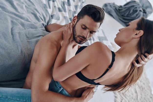 L'amour vrai. vue de dessus d'un beau jeune couple semi-habillé se liant tout en passant du temps à la maison