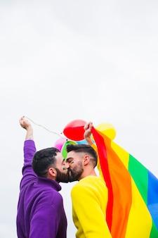 Amoureux gays s'embrassant lors du défilé de la fierté lgbt