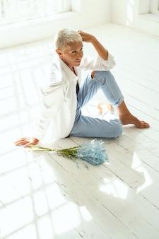 Amoureux. gentille femme assise sur le sol et démontrant sa flexibilité