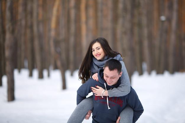 Amoureux heureux en hiver sur fond de forêt enneigée à l'extérieur
