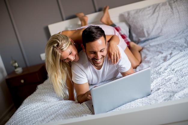 Amoureux intimes utilisant un ordinateur portable allongé sur le lit dans la chambre