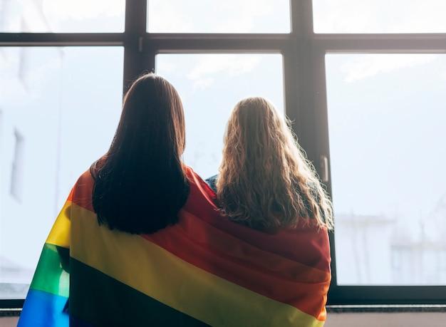 Amoureux lesbiennes enveloppés dans le drapeau lgbt