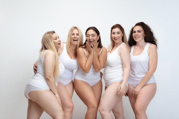Amoureux de moi-même. portrait de belles jeunes femmes de taille plus posant sur fond blanc. heureux modèles féminins souriants riant ensemble. concept de corps positif, beauté, mode, style, féminisme.