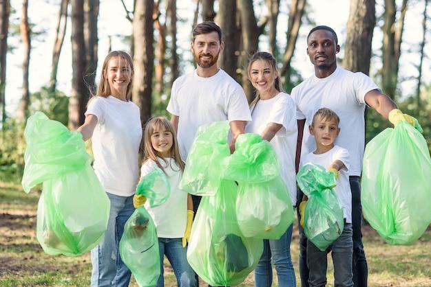 Les amoureux de la nature métisse et multi-âge montrent des sacs en plastique avec des déchets qu'ils ont ramassés au parc.