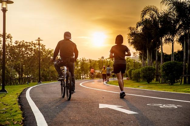 Les amoureux roulent à vélo et courent sur la route dans le parc