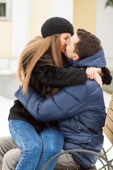Les amoureux s'embrasser sur le banc