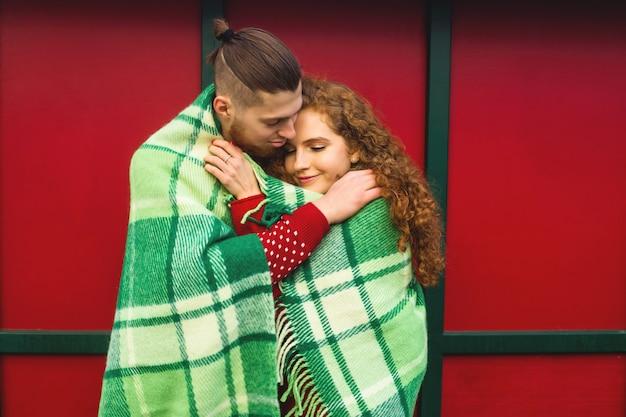 Les amoureux s'étreignent et sourient joyeusement dans une atmosphère de noël chaleureuse.