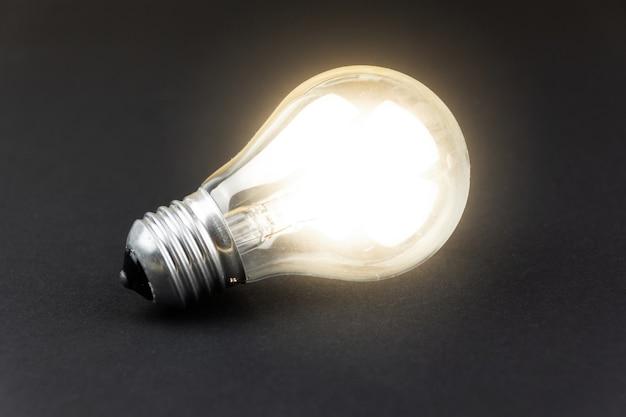 Une ampoule allumée sur un carton noir