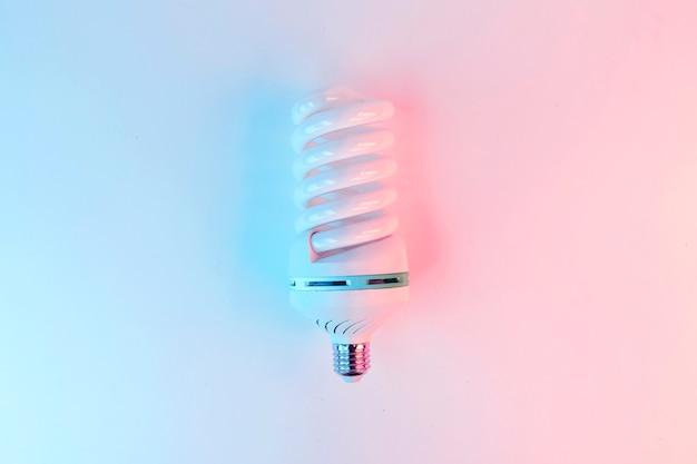 Ampoule allumée dans des couleurs holographiques violettes et bleues dégradées vives à plat vue de dessus