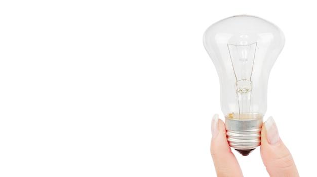 Ampoule allumée tenue en arrière-plan de la main