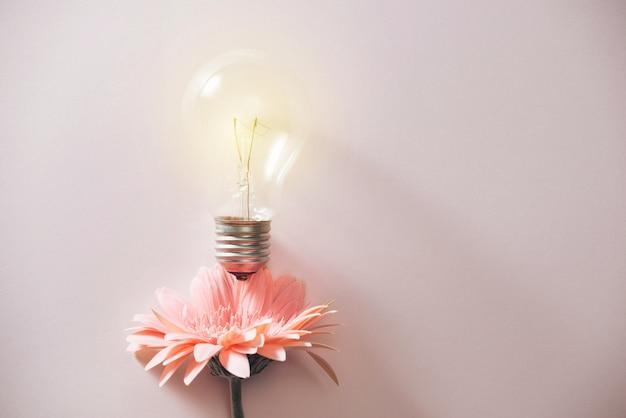 Ampoule avec belle fleur autour sur fond rose