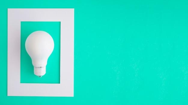 Ampoule blanche dans le cadre blanc sur fond vert