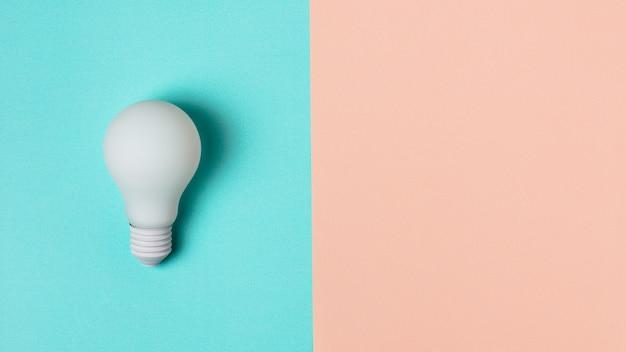 Ampoule blanche sur fond bleu et rose