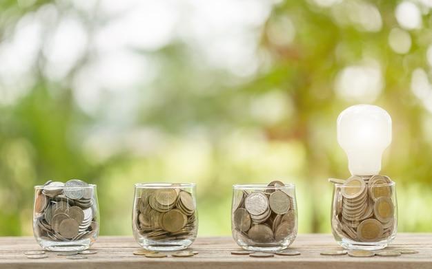 Ampoule blanche et pièce en pot transparent sur table en bois. économies d'argent pour le coût du concept énergétique